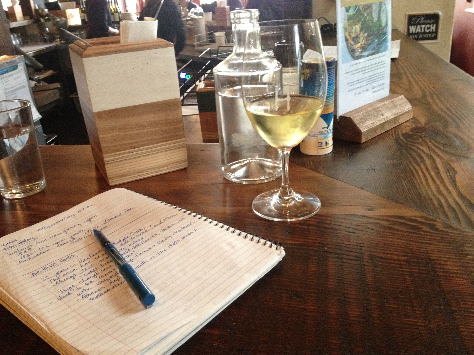 Research notes and a glass of local white in the Yarra Valley