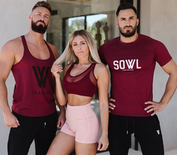 men's activewear red top with black joggers and women's activewear red sports bra with pin