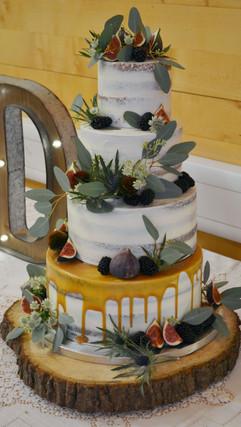 asymetric semi naked caramel drip wedding cake