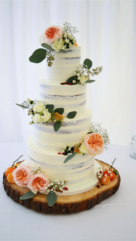 4 tier semi naked wedding cake with clementines and juliette roses