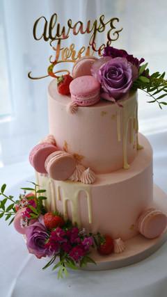 blush pink wedding cake with drip and macarons