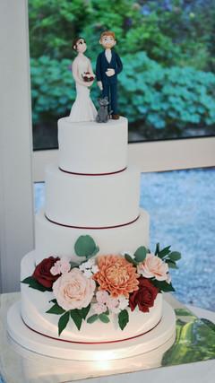 white wedding cake with burgundy and blush sugar flowers