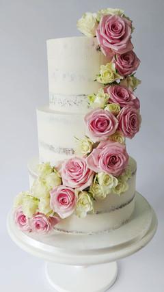 semi naked wedding cake with fresh cascading roses