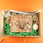 Drewniany wieszaczek z motywem paryskiego roweru, zapakowany w eko karton z papierowym wypełniaczem.