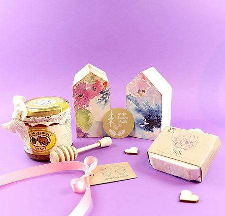 Kobiecy zestaw prezentowy na Dzień Babci, Dzień Mamy i Dzień Kobiet. Drewniane domki ozdobione różowymi i fioletowymi kwiatami, miód z mazurskiej pasieki, naturalne mydełko z dodatkiem soli himalajskiej.