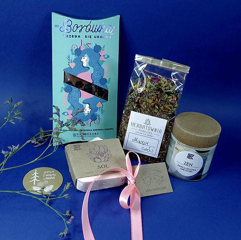 """Składniki zestawu prezentowego """"Mazurski relaks"""" sfotografowane na niebieskim tle. Zdjęcie udekorowane z lewej strony gałązką małych fioletowych kwiatków. Czekolada rękodzielnicza z borówką w niebieskim kartoniku z grafiką kobiety z nazwą """"Borówką trzeba się urodzić"""", lawendowe ręcznie robione mydło z dodatkiem soli himalajskiej o nazwie """"Sól"""", zapakowane w ekologiczną tekturę. Dwie etykiety pracowni """"Ale kot! Ale żaba!"""" ułożone pomiędzy elementami zestawu. Mieszanka herbat o nazwie """"Miłych snów"""" zapakowana w foliową przezroczystą torebkę. Po prawej stronie świeca sojowa """"ZEN"""" na dobry sen, kompozycja lekkich zapachów: lawenda, drzewko herbaciane i pomarańcza, w szkle 100 ml, zakrętka z wiórów drewnianych."""