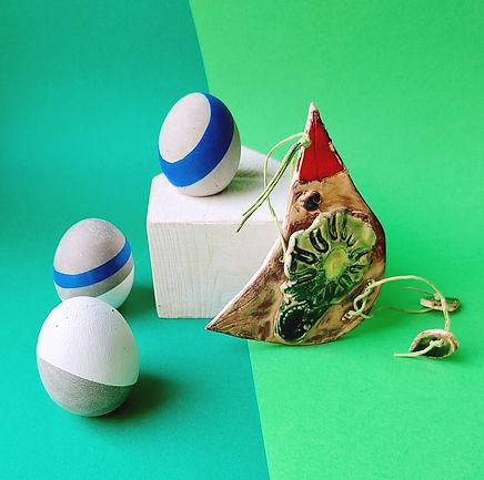 Zestaw mazurskich ręcznie robionych dekoracji sfotografowanych na zielonym tle. Betonowe jajeczka pomalowane w białe i granatowe paski. W zestawie ceramiczna zawieszka – ptaszek w kolorach ziemi, skrzydełko w kształcie zielonego kwiatka, z czerwonym dziubkiem. Jedno z jajeczek, z granatowym paskiem, postawione na białym drewnianym domku.