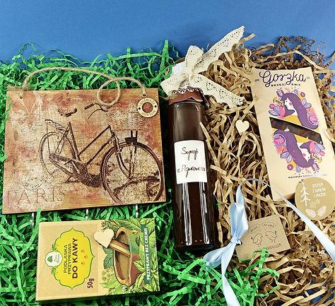 Upominek zapakowany w pudełko z naturalnym wypełniaczem papierowym, zawiera wieszaczek, syrop z pigwowca, przyprawę do kawy i gorzką czekoladę.