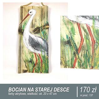 Bocian ręcznie malowany na starej desce. Deska z zawieszką z grubego sznura. Bocian stoi w trawie. Na desce wyraźnie widoczne duże sęki. Obraz pionowy, szerokość deski 20 cm, wysokość 47 cm