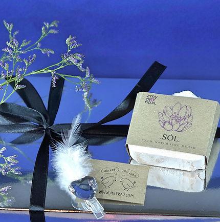"""Zestaw prezentowy zapakowany w eleganckie srebrne pudełko przewiązane czarną wstążką. Pudełko sfotografowane na granatowym tle, ozdobione gałązką małych fioletowych kwiatków. Na pudełku etykieta pracowni """"Ale kot! Ale żaba!"""" nadrukowana na papierze kraftowym. Na pudełku ręcznie robione mydło lawendowe z solą himalajską, w opakowaniu zero waste."""