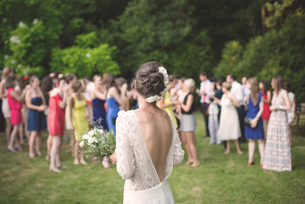Bride about to throw her bouquet at outdoor wedding