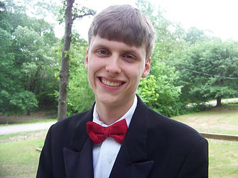 Zach is ready to granduate. He is dressed in a suit and red bow tie with a huge smile.