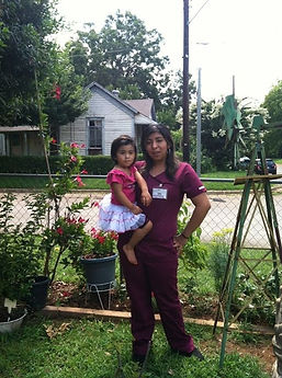 Laura and holding her daugher. Laura is dressed in her work uniform.