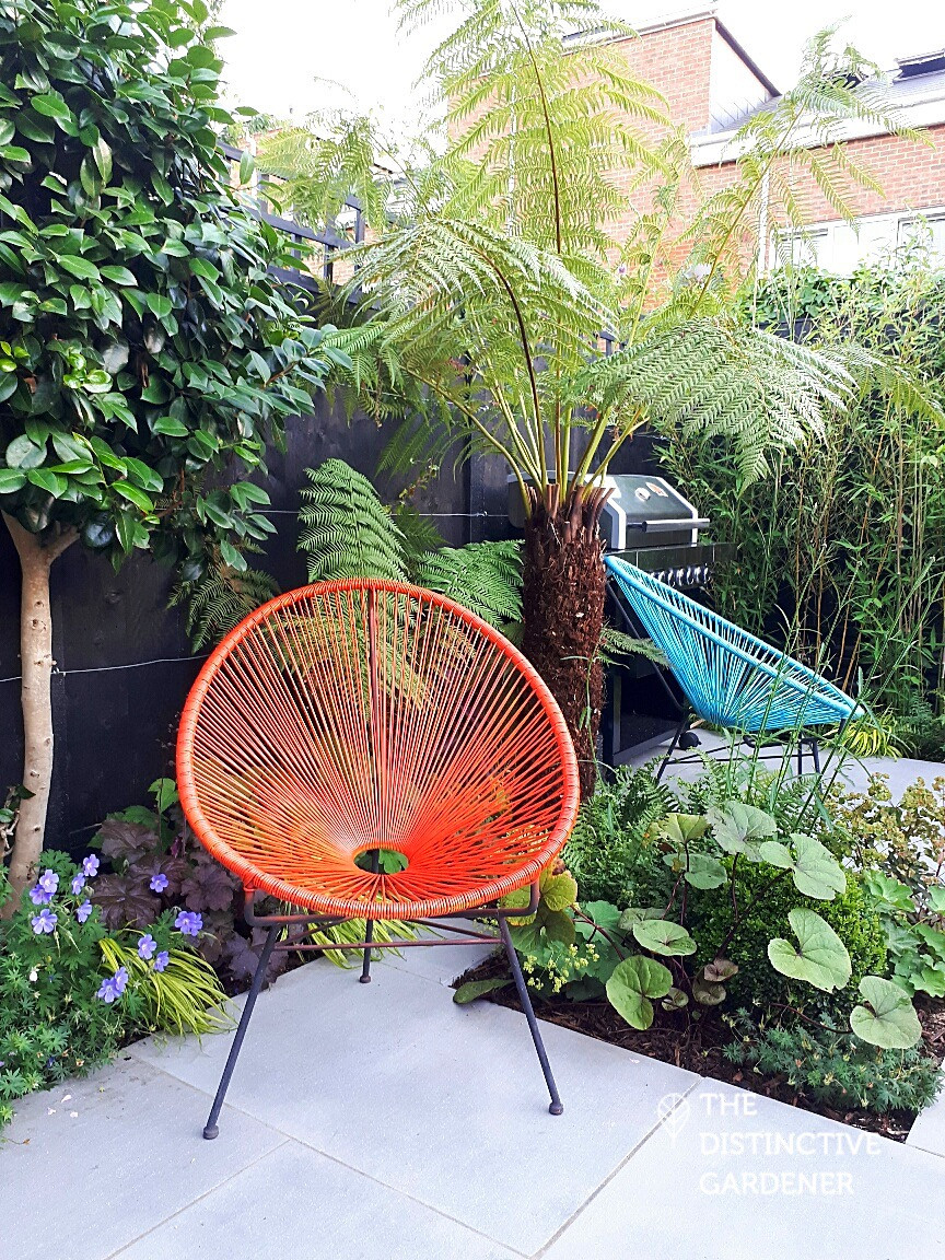 The garden's BBQ area, disguised by palm tree fronds