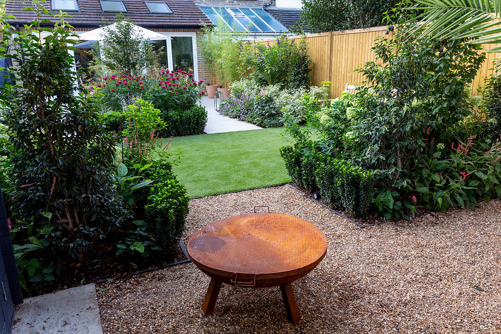 Wide garden lawn with bench and borders
