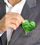 Businessman holding a green heart leaf /