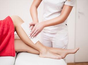 Beautician waxing woman a leg at salon /