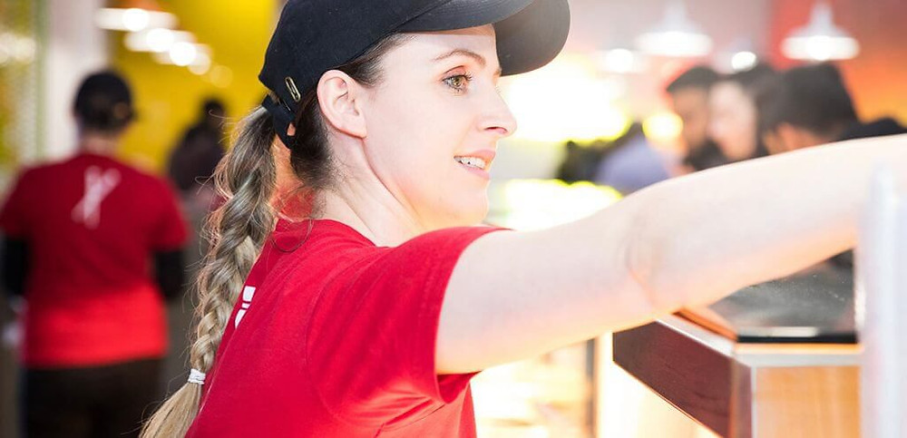 woman in chopstix uniform serving customers