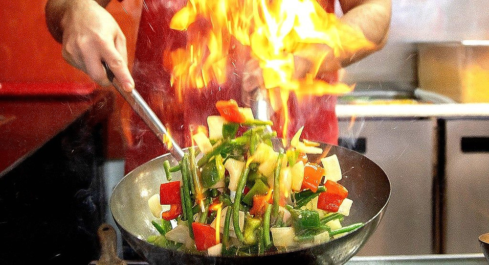 close up of wok with chef sautéing vegetables