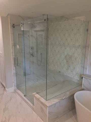 Frameless glass shower enclosure showcases beautiful tile