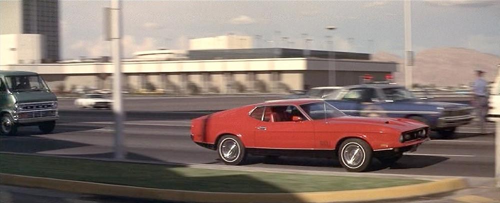 Ford Mustang Match 1 (1971) color rojo, atraviesa Las Vegas