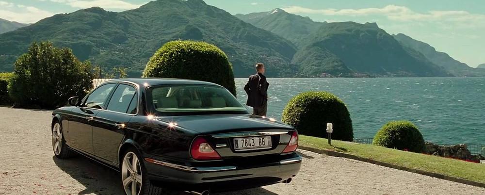 James Bond (Daniel Craig), de pie frente a un lago junto a su Jaguar XJR