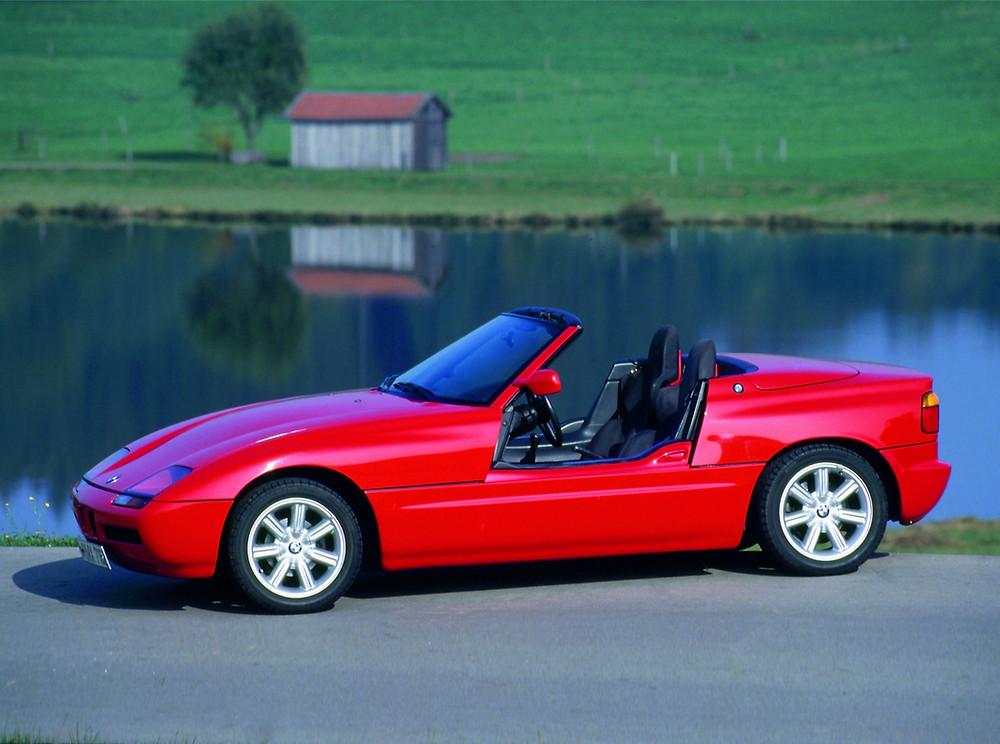 BMW Z1 rojo con las puertas abajo junto a un lago