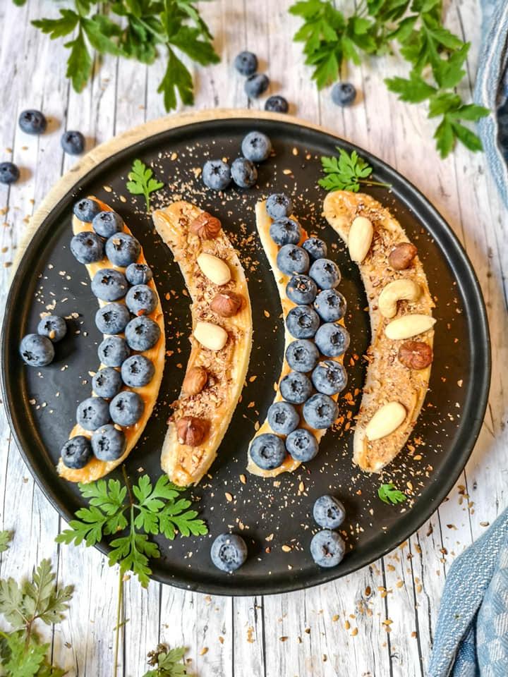 Erdnuss-Mus, Heidelbeeren und Nüsse garnierte Bananenbrote