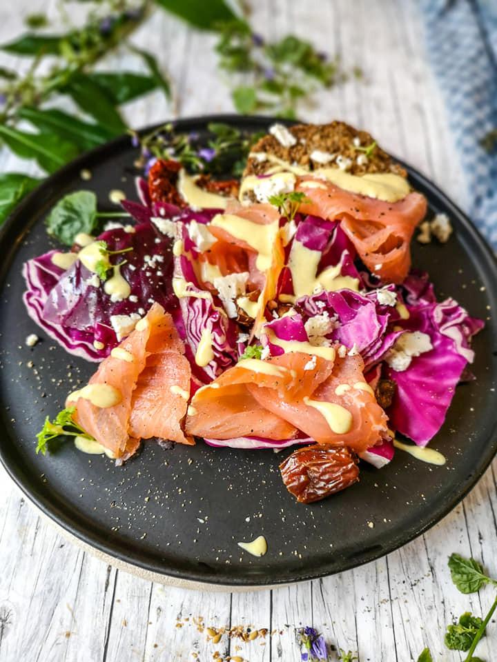 Salat mit Rotkohl, Lachs, Feta, getrockneten Tomaten und Datteln in aromatischer Honig-Senf-Sauce