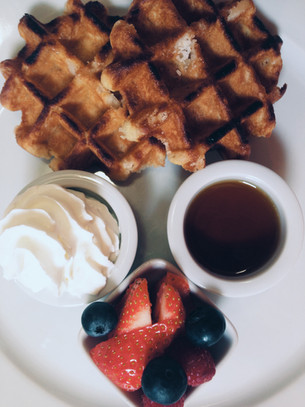 Sweet Belgium Waffles served with maple syrup, berries and cream
