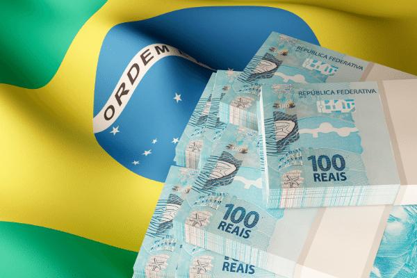 Bandeira do Brasil 7 maços de notas de 100 reais, mostrando como gerar recursos financeiros com markting político, com site no wordpress.
