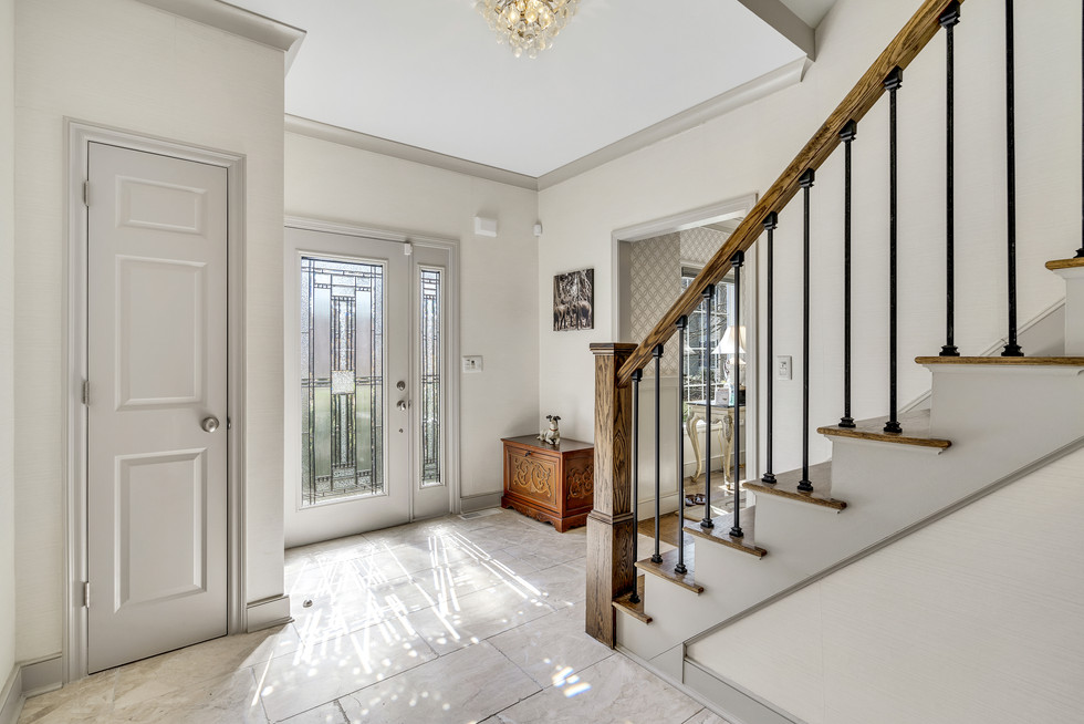 Beautiful foyer with tile and wood banister custom build in real estate photograph by Allard Media Group