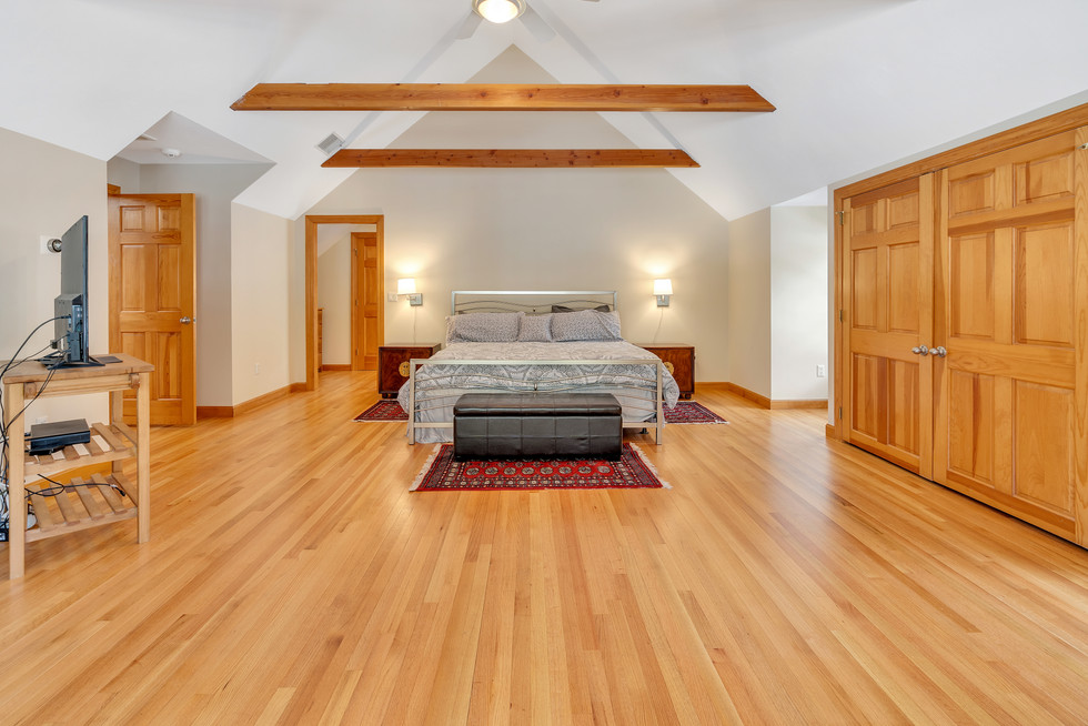 Spacious beautiful custom build master bedroom with hardwoods in real estate photograph by Allard Media Group