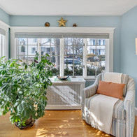 Cozy sunroom with wide windows in real estate photograph by Allard Media Group
