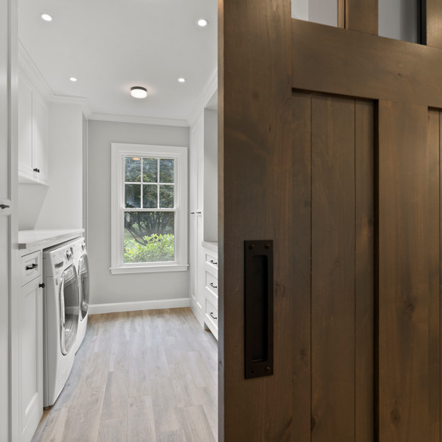 Custom pantry and laundry room in luxury home with beautiful barn door real estate photography with high-end editing shot by real estate photographer Allard Media Group
