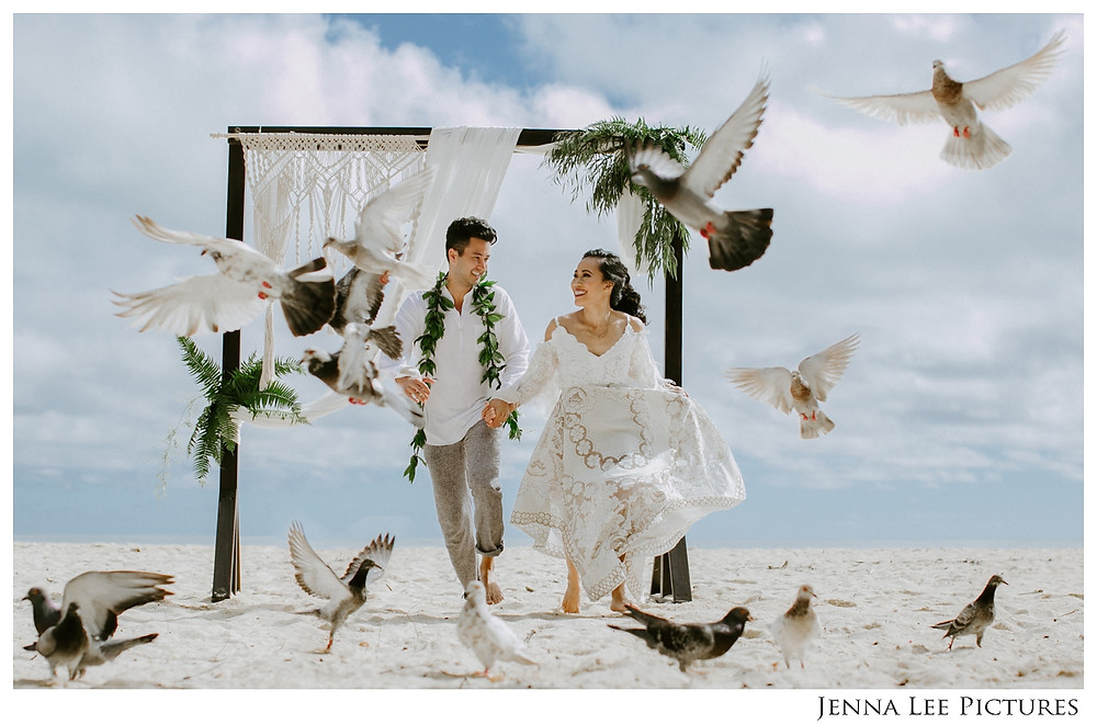 A wedding couple runs through a flock of birds flying about them on the beach in Hawaii during their Hawaii elopement on Oahu