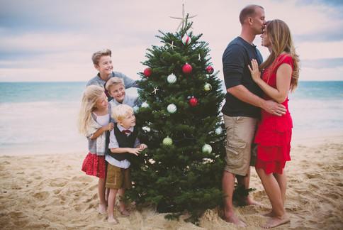 Camily Christmas photos. Oahu. hawaii an adorable family decorates a christmas tree on the beach.