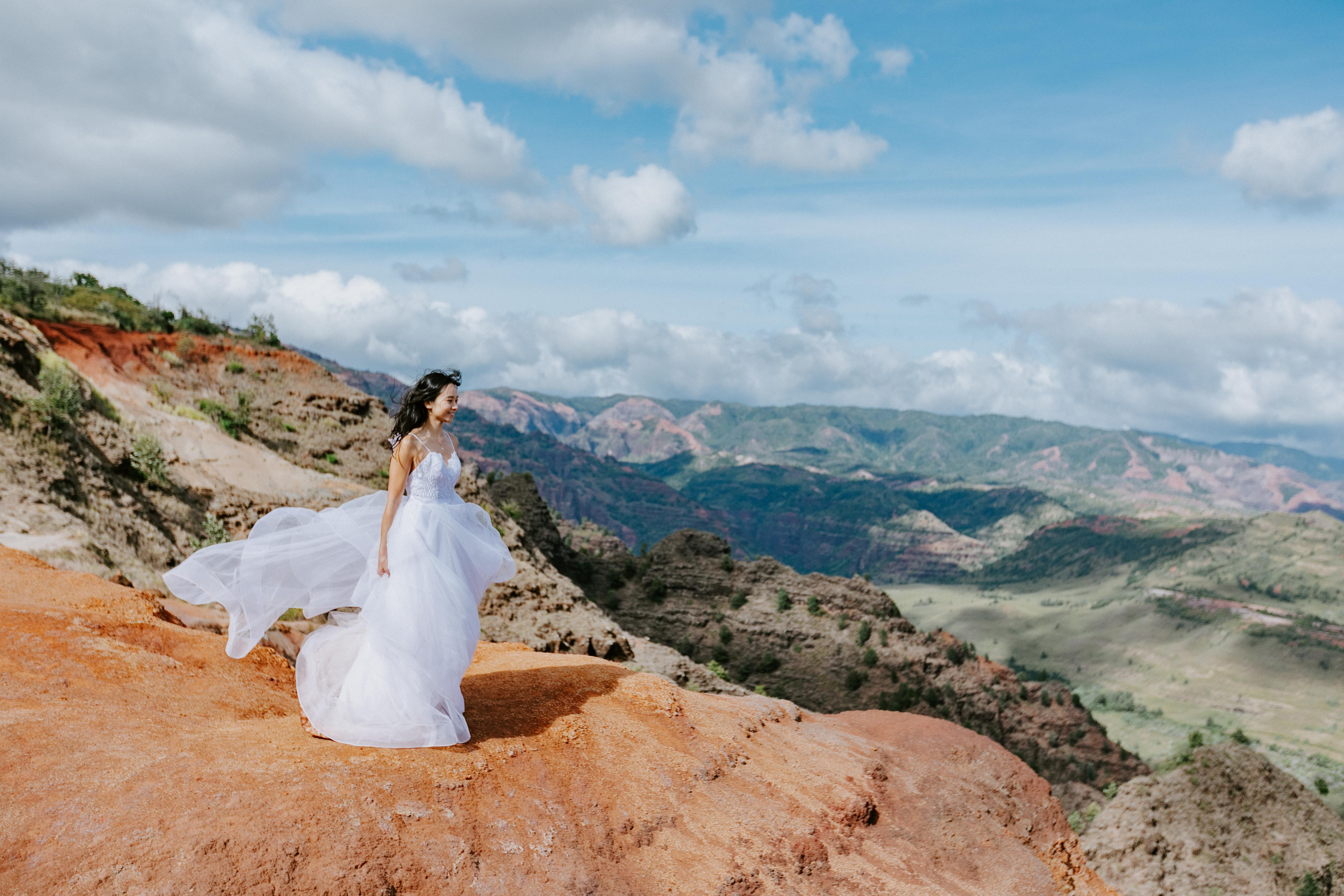 An adventurous bride stands on the edge of Waimea Canyon in Kauai during her adventure wedding sessi