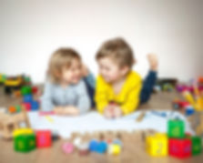 Preschool boy and girl play on floor wit