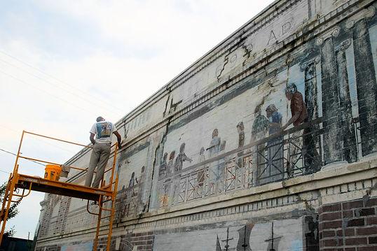 Norton Art restoring The Promenade Mural in Bay St. Louis, MS