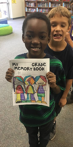 CES Student shows off his last day of Second Grade project in the library.