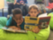 Two CES students reading some of the new books purchased for the library.