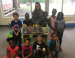 CES Librarian, Mrs. Johnson, and several students with some of the newly purchased books.