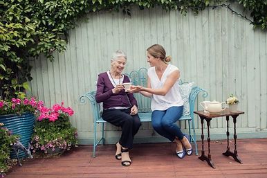 Live-in Carer sitting with an elderly client on a bench
