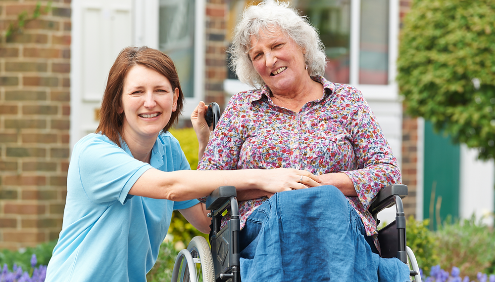 Live-in Carer with and elderly woman in a wheelchair with Multiple Sclerosis
