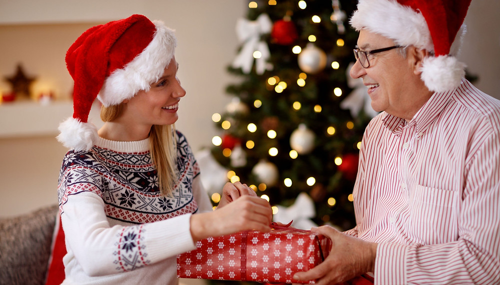 Live-in carer giving elderly man a Christmas present