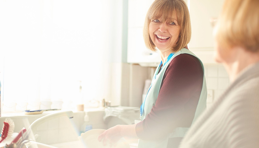 Carer smiling whilst helping an elderly client with washing up