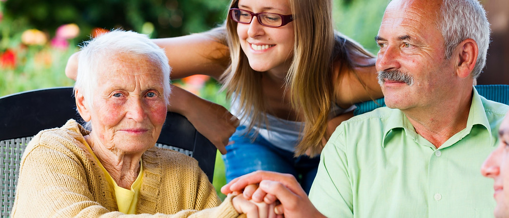 Elderly woman with dementia sitting with elderly husband and a Live-in Carer