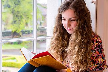 Yasmin Frampton sat in a window reading a book