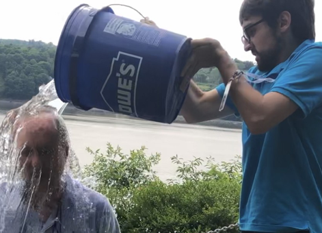 Sebastien dumps bucket of water on man.
